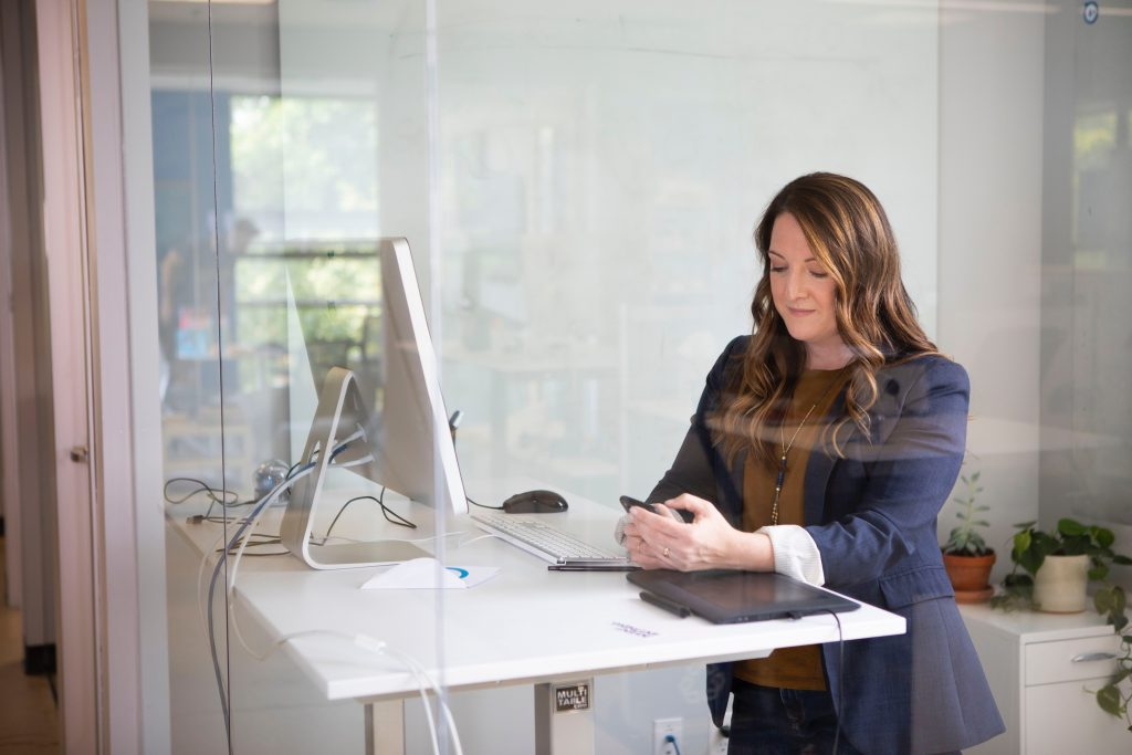 Woman on her phone standing inside her modern office space.