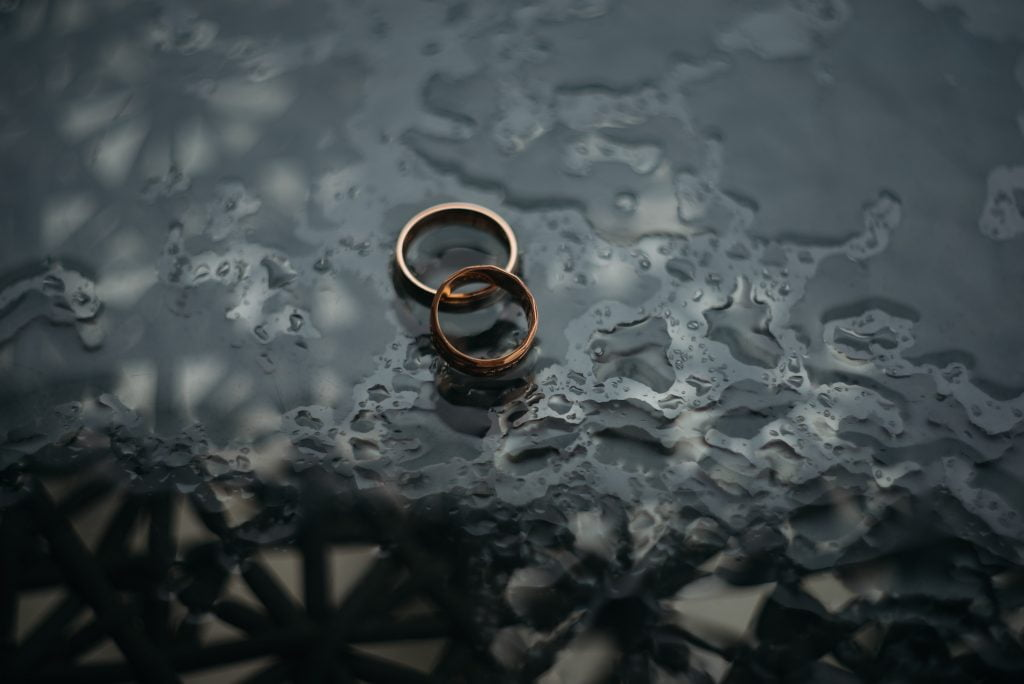 Two wedding rings sitting on a dark rainy table representing divorce.
