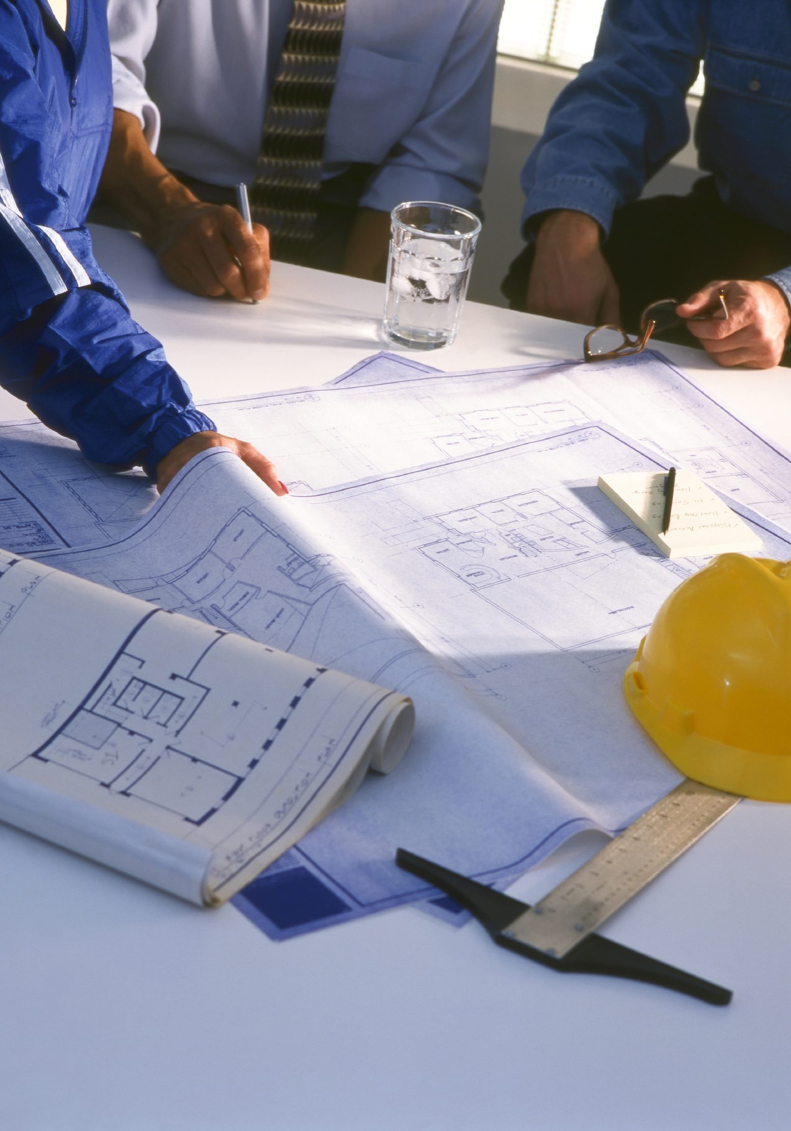 Three Building Professionals Reviewing Construction Blueprints.