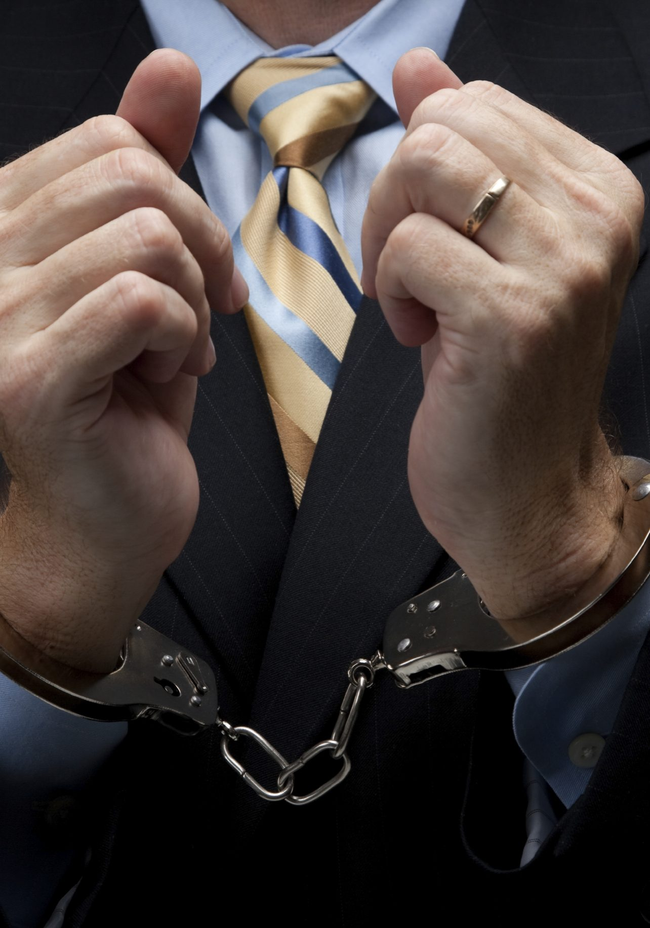 A man in a blue business suit holding hands in handcuffs in front of his chest- white collar or corporate crime